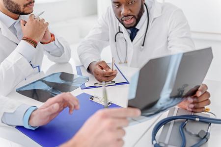 Skillful traumatologists discussing radiograph of human leg
