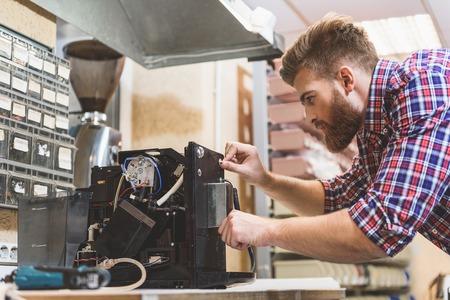 심각한 사람이 깨진 커피 기계를 수리 스톡 콘텐츠