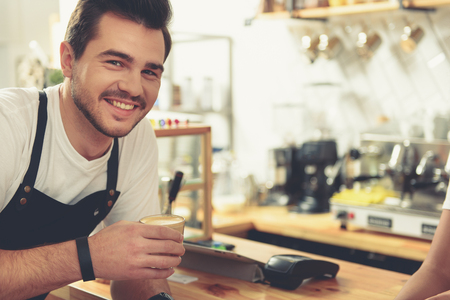 candy store: Smiling man taking coffee in comfortable candy store