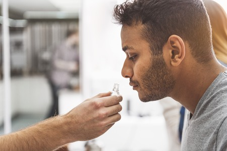 Concentrated serious man smelling aroma Stock Photo