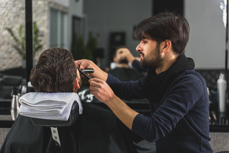 coiffeur: Confident barber serving customer at salon