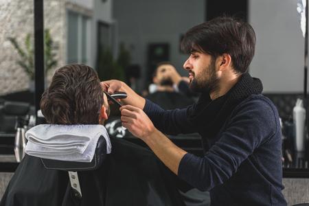 shearer: Confident barber serving customer at salon