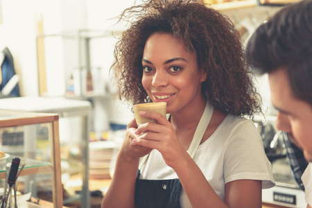 Outgoing woman keeping appetizing cup of latte in hands Stock Photo