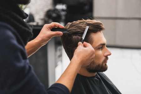 Male client getting haircut by hairdresser Reklamní fotografie