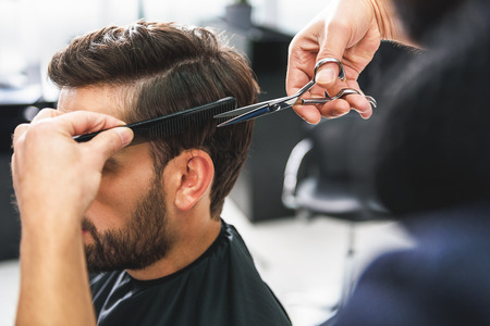 Barber using scissors and comb
