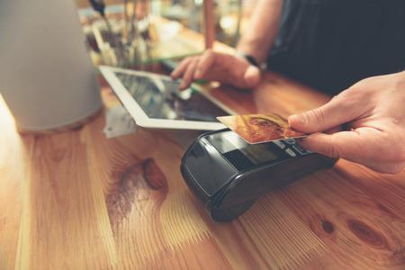 Barista prendendo la carta di credito per fare il pagamento per il visitatore Archivio Fotografico