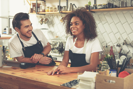 the brewer: Outgoing baristas speaking during their work in sunny cafe Stock Photo