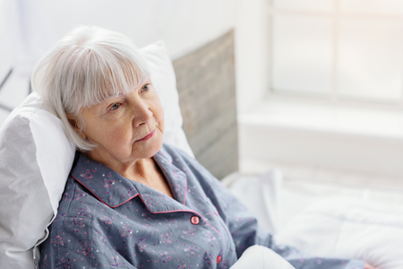 inpatient: Female retiree lying in bright apartment of clinic Stock Photo