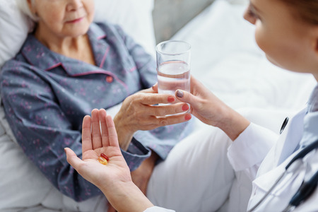 Physician holding drug and drink to pensioner Stok Fotoğraf