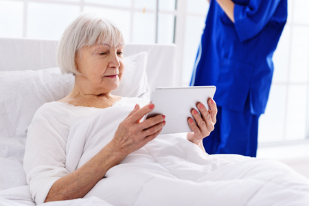 Smiling grandmother watching at screen in white hospital room