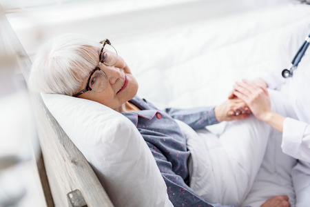 Cheerful old woman situating in cot in hospital