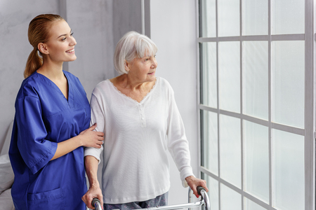 pensioner: Cheerful pensioner walking at time bucket in room of clinic