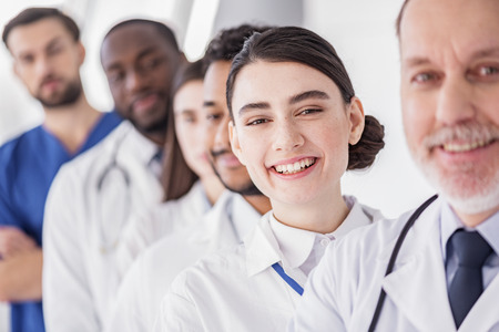 auscultoscope: Smiling doctor situating near her colleagues in clinic