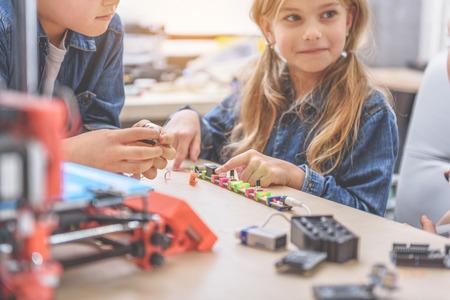 Het gelukkige meisje zit naast jongen dichtbij houten bureau, hoogtepunt van verschillend materiaal. Ze keek opzij Stockfoto