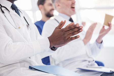 Physician applauding at conference in hospital