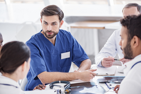 met: Thrilled doctor arguing with associates during meeting Stock Photo