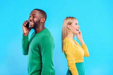 Happy man and woman communicating on smartphones Stock Photo