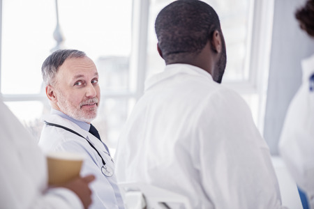 auscultoscope: Happy physician watching at report during conference Stock Photo
