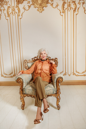 Mature lady resting on gorgeous chair Stock Photo