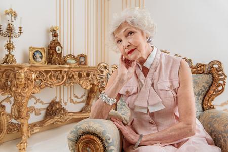 Elegant senior woman sitting on luxury armchair