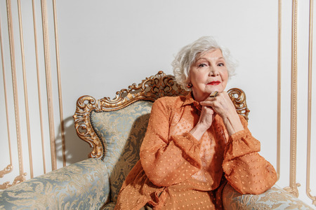 Pensive mature lady relaxing on expensive chair