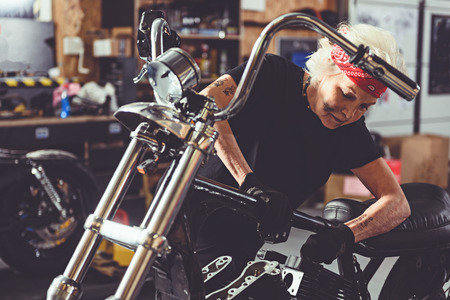 Serene granny reconditioning motorcycle in garage