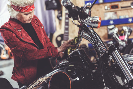 Calm beneficiary burnishing motorcycle in garage