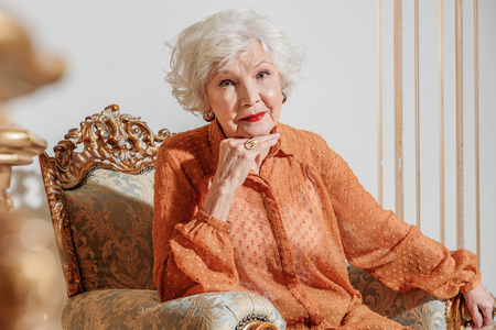 Alone senior woman resting on luxury armchair Stock Photo
