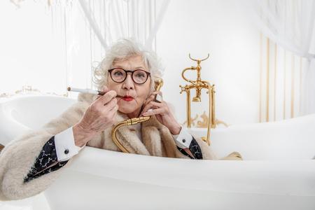 Rich old woman having fun in bathroom Stock Photo
