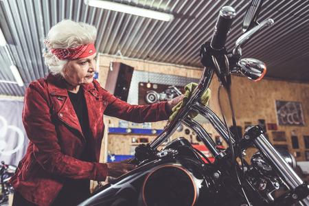 pensioner: Thoughtful pensioner polishing bike in mechanic shop Stock Photo