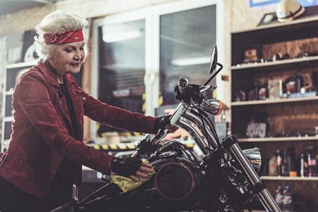 pensioner: Outgoing pensioner burnishing bike in mechanic shop