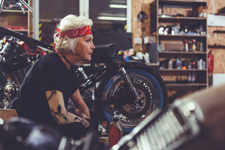 pensioner: Thoughtful pensioner making machine maintenance in garage