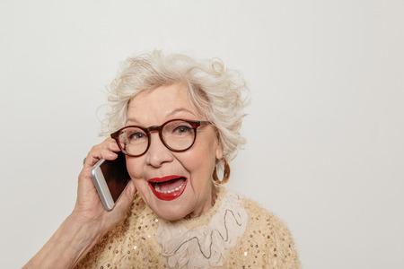 휴대 전화로 말하기 흥분된 성숙한 여인