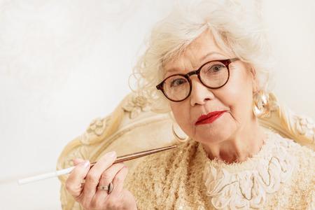 Serious old woman smoking cigarette Stock Photo
