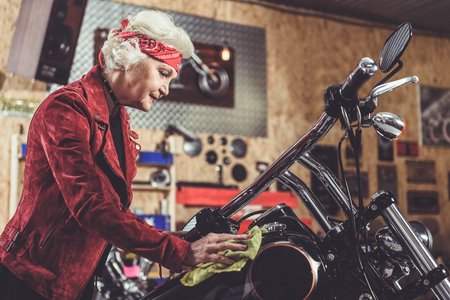 Outgoing pensioner cleaning motorcycle in garage