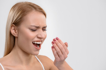 Blond girl exhaling unpleasant air smell on hand