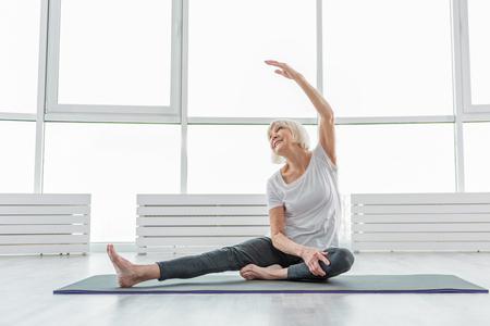 Blije oude vrouw ondergaat ochtendgymnastiek Stockfoto