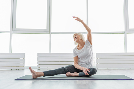 Joyful old woman undergoing morning exercises