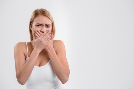 Nervous young woman closing mouth with shame