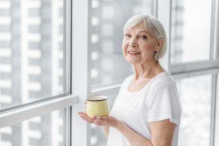 温かい飲み物を楽しんで幸せなシニア女性