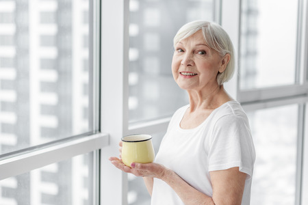 Happy senior lady enjoying hot drink