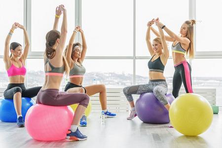 levantar peso: Feliz mujeres deportivas en el gimnasio