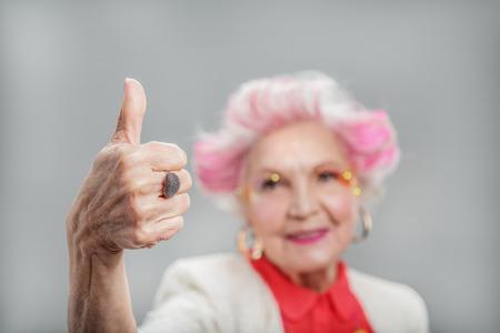 Heureuse dame senior qui pose en studio