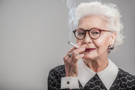 Happy aged lady enjoying ciggy Фото со стока