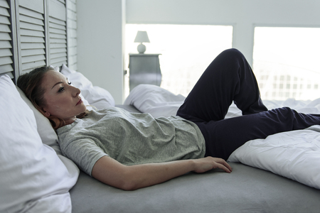 bedstead: Frustrated woman lying on bedstead Stock Photo