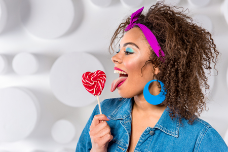 Cheerful young female eating candy