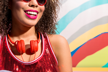 Beaming woman wearing earphones against variegated picture Stock Photo