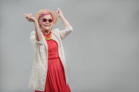 Gelukkige mooie hogere dame die zonnebril en hoed draagt