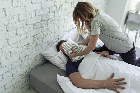 Mad wife is covering face of husband with pillow and trying to suffocate him Stock Photo