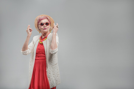 Cheerful aged woman in sunglasses enjoying music Stock Photo